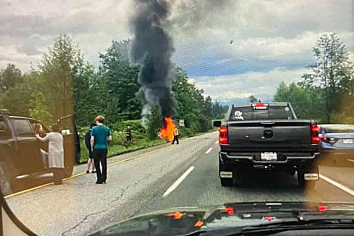 Will Vader, seen on the left wearing the green shirt, pulled the woman and her baby from the car minutes before it burst into flames. Facebook photo.