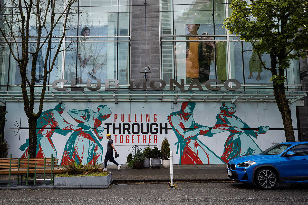 A man walks past a closed Club Monaco store with messages and artwork painted on the boarded up windows and doors, in Vancouver, on Sunday, May 17, 2020. THE CANADIAN PRESS/Darryl Dyck
