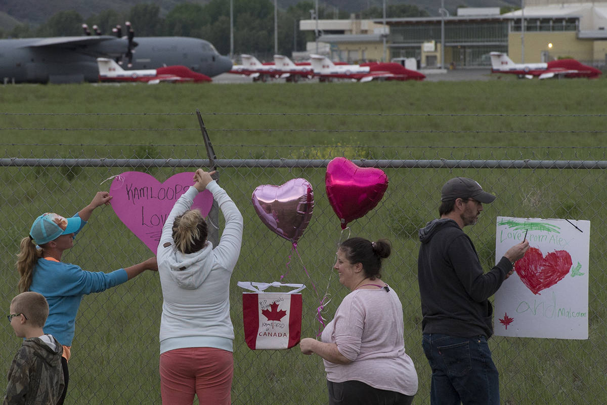 Canadian Forces Snowbirds planes are seen in the background as people place hearts and signs on the fence surrounding the airport in Kamloops, B.C., Sunday, May 17, 2020. One member of the Canadian Armed Forces has died and another is injured after a Snowbird plane crashed in a residential area of Kamloops, B.C., on Sunday while on a cross-country tour meant to impart hope during the COVID-19 pandemic. THE CANADIAN PRESS/Jonathan Hayward