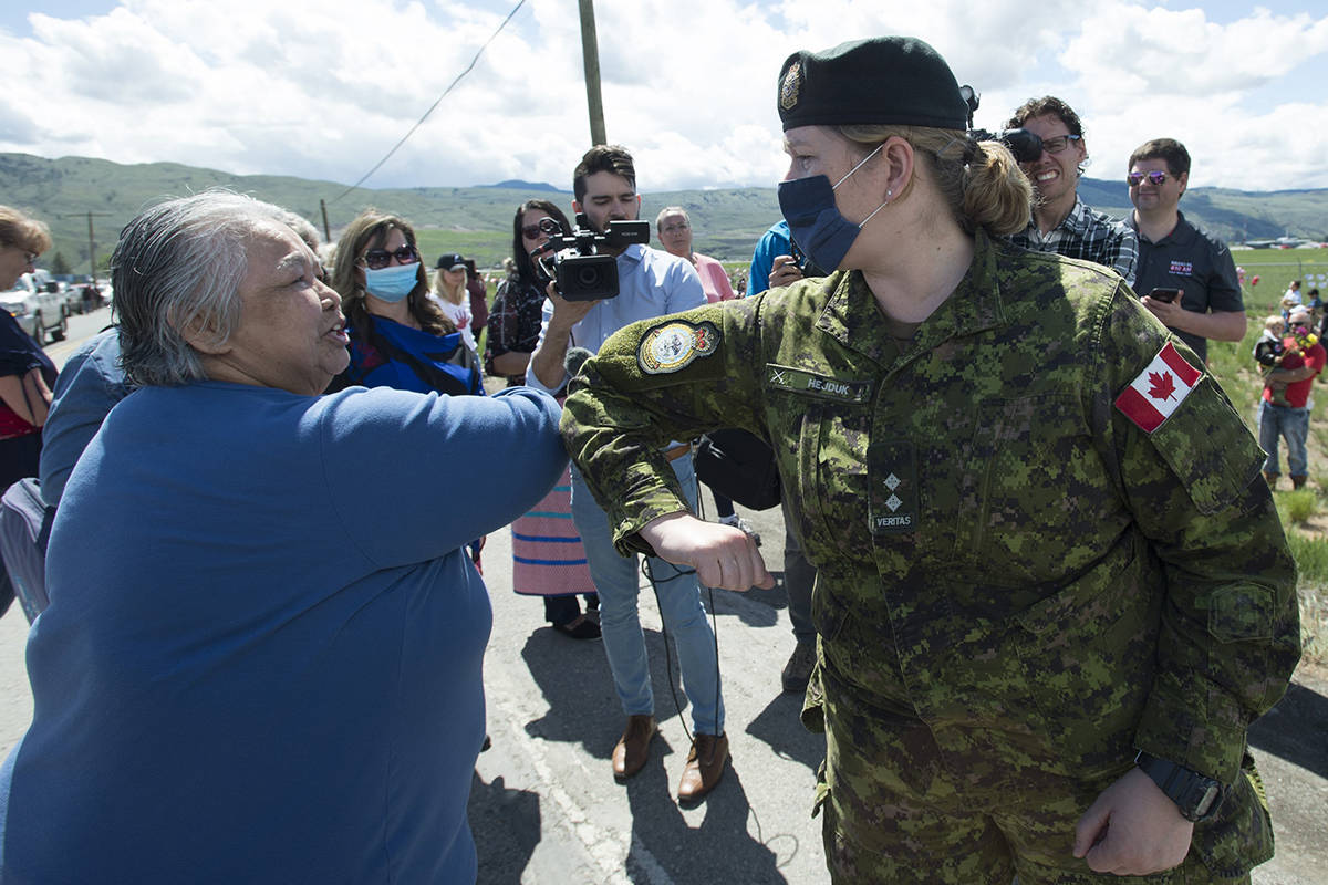 Royal Canadian Air Force Public Affairs Officer Lt. Alexandra Hejduk, right, is thanked for her service with a elbow bump by a first nations elder at the Kamloops airport in Kamloops, B.C., Monday, May 18, 2020. People are gathering at the airport to honour Canadian Forces Snowbirds Capt. Jenn Casey who died Sunday after the jet she was in crashed after takeoff. THE CANADIAN PRESS/Jonathan Hayward