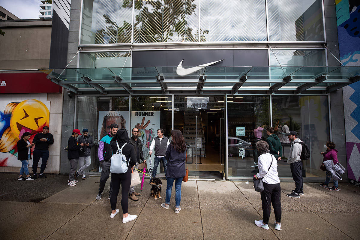 People wait to enter a Nike store on its first weekend open after a lengthy closure due to COVID-19, in Vancouver, on Sunday, May 17, 2020. THE CANADIAN PRESS/Darryl Dyck