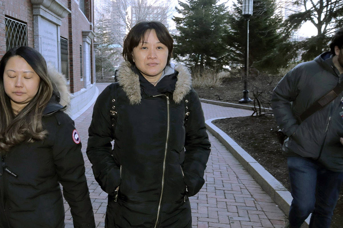 Xiaoning Sui, center, a Chinese national residing in British Columbia, Canada, leaves federal court, Friday, Feb. 21, 2020, in Boston, after pleading guilty to paying $400,000 to get her son into the University of California, Los Angeles, as a fake soccer recruit. (AP Photo/Charles Krupa)