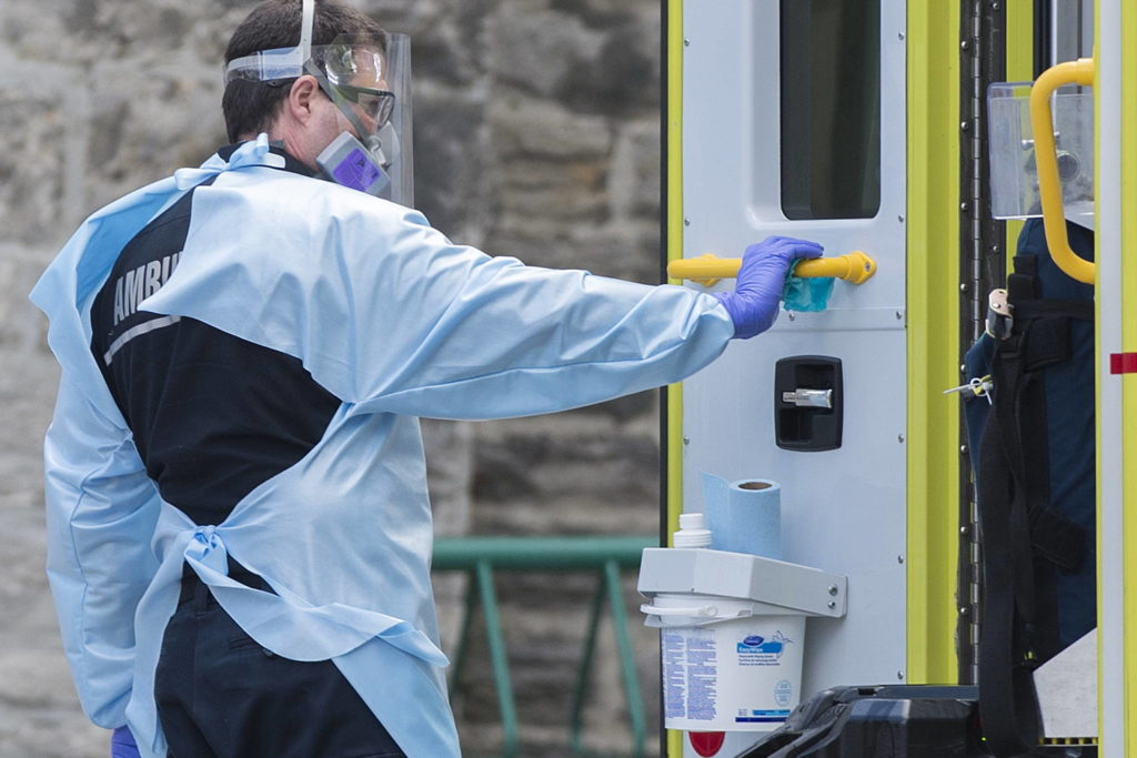 A paramedic disinfects the handle on the door of an ambulance outside the Hotel-Dieu hospital in Montreal, Sunday, May 3, 2020, as the COVID-19 pandemic continues in Canada and around the world. THE CANADIAN PRESS/Graham Hughes