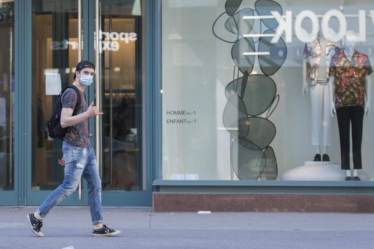A man wearing a face mask gestures as he walks by a store on Sainte-Catherine street in Montreal, Monday, May 18, 2020. Shopping for clothes used to be a relatively simple process three months ago: walk into a store, try on a number of items, buy what you want, leave the rest. THE CANADIAN PRESS/Graham Hughes