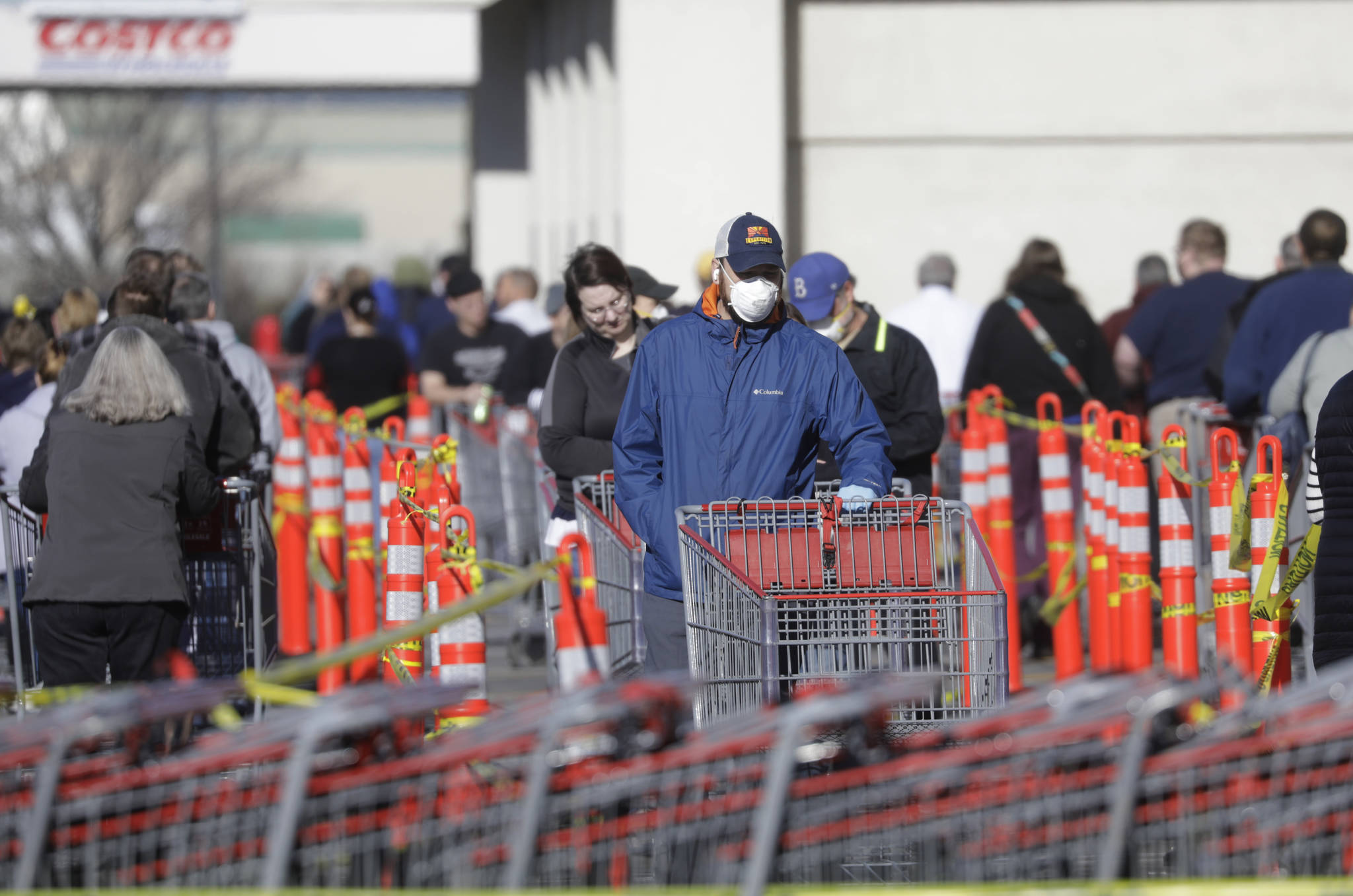 A person wears a mask as he stands in line at Costco Saturday, April 4, 2020, in Salt Lake City. The Centers for Disease Control and Prevention is now advising Americans to voluntarily wear a basic cloth or fabric face mask to help curb the spread of the new coronavirus. (AP Photo/Rick Bowmer)