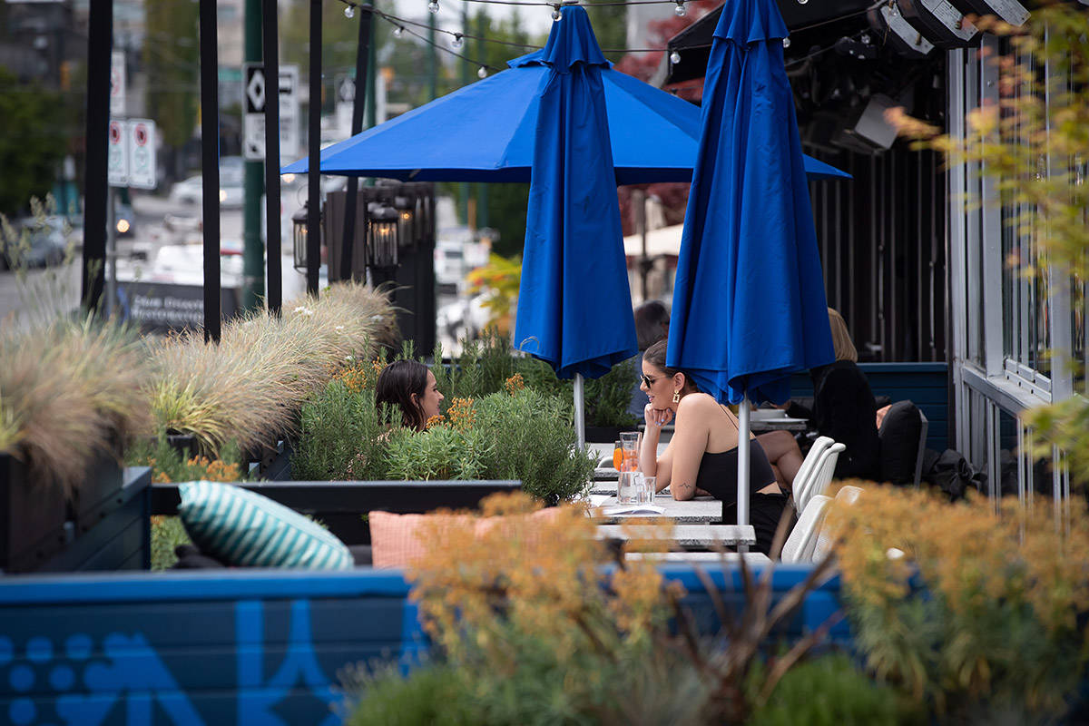 Two women have drinks on the patio at an Earls restaurant, in Vancouver, on Tuesday, May 19, 2020. British Columbia began phase two of the reopening of its economy Tuesday, allowing certain businesses that were ordered closed due to COVID-19 to open their doors to customers if new health and safety regulations are followed. THE CANADIAN PRESS/Darryl Dyck