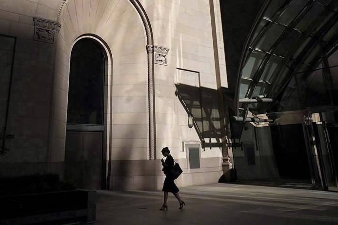A woman walks through Toronto's financial district on July 30, 2018. With women bearing the brunt of the COVID-19 pandemic, federal officials are trying to figure out how recovery efforts can help get women back to work, earning more money and securing more stable jobs. THE CANADIAN PRESS/Graeme Roy