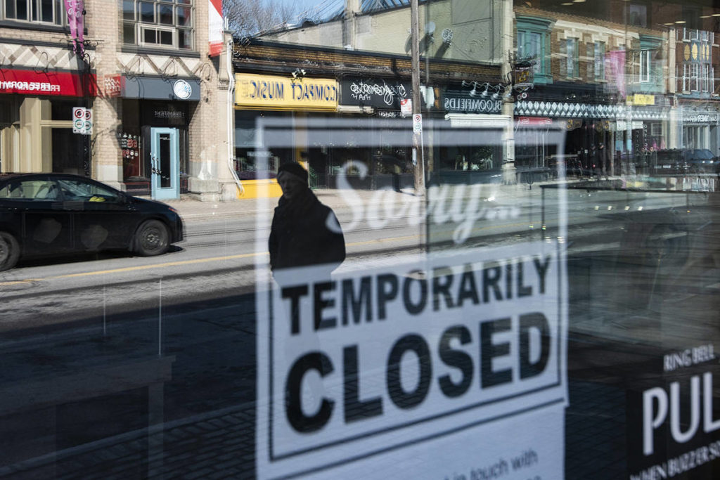 Storefronts in Ottawa's Glebe neighbourhood are reflected in a sign indicating the temporary closure of a business to prevent the spread of COVID-19, on Tuesday, March 24, 2020. The pandemic has meant a slew of commercial renters — from the country's smallest businesses to the behemoths — have had to have a tough conversation with their landlord about how they are unable to cover rent. THE CANADIAN PRESS/Justin Tang