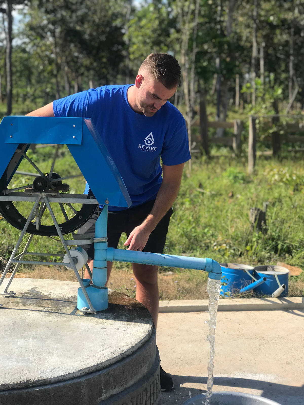 David Moerman pumps water out of a well in Pursat, Cambodia in December, 2019. Moerman's company, Revive Washing, funded the water well. (Photo: Submitted)