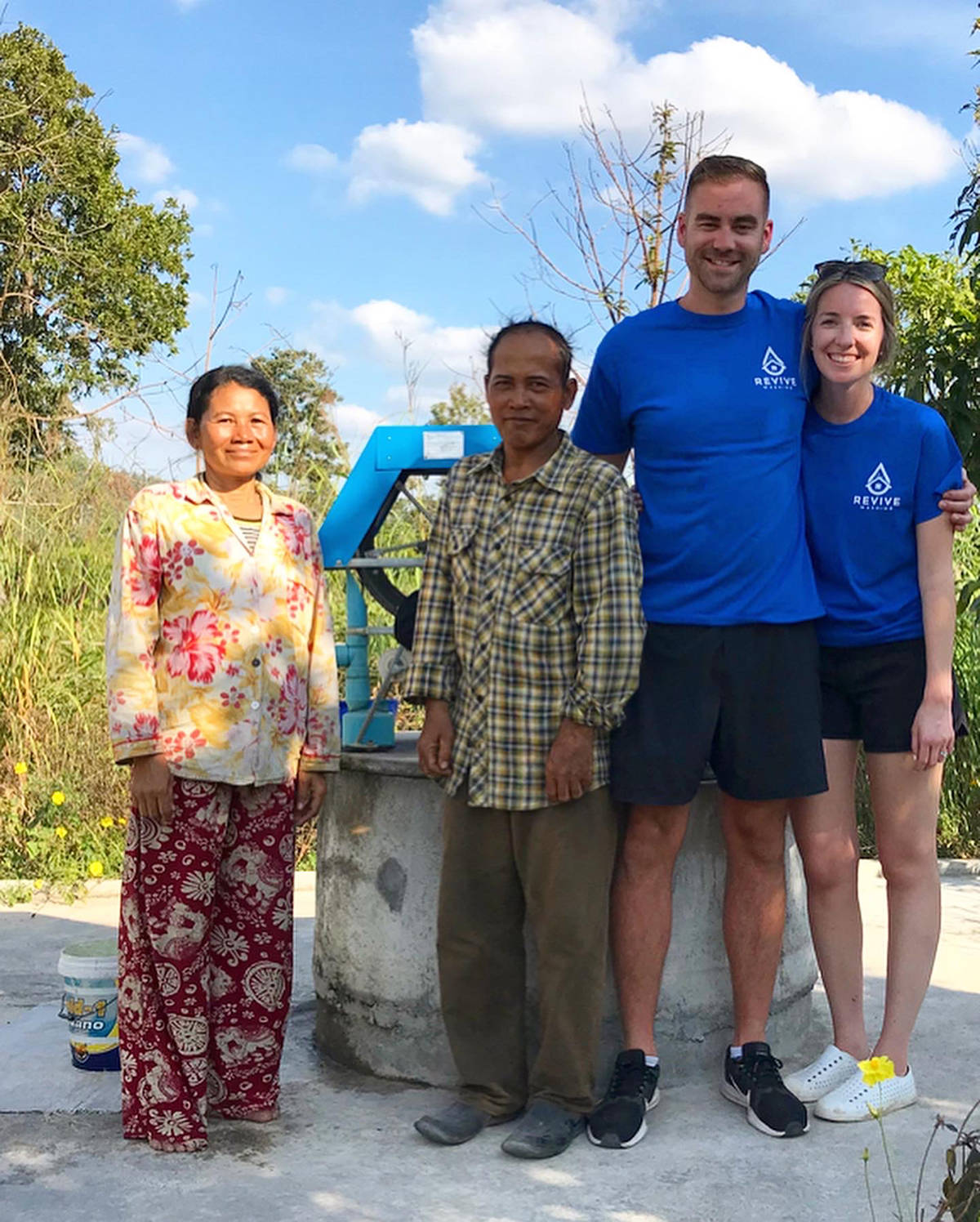 David Moerman and his wife Alex stand with a local family in December, 2019, in Pursat, Cambodia in front of a water well Moerman's company, Revive Washing, funded. (Photo: Submitted)