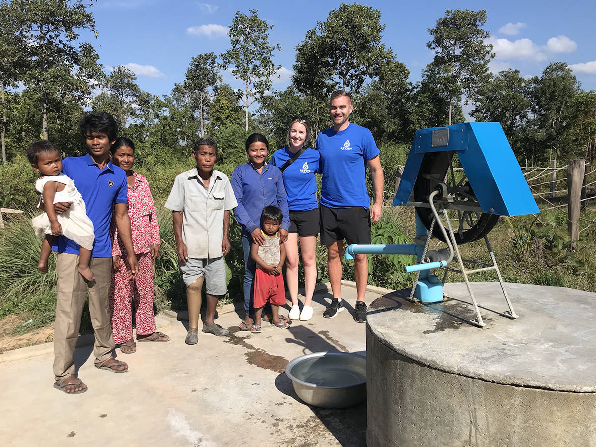 David Moerman and his wife Alex meet with a local family near a well (foreground) in Pursat, Cambodia in December, 2019. Moerman's company, Revive Washing, funded the well. (Photo: Submitted)