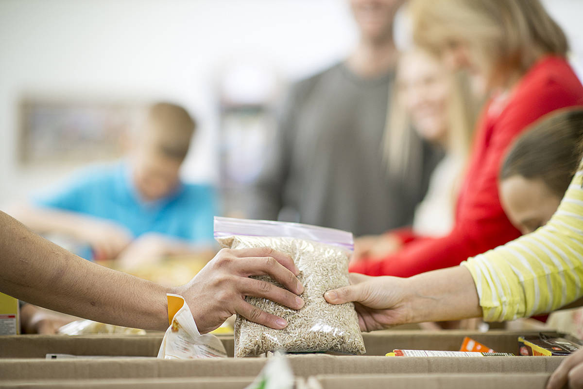Envision Financial launched a community response fund to help local charities during this time of crisis. They are hoping to encourage local charities to apply. A group of volunteers (above) working at a food bank were sorting non-perishable food items into boxes. (Special to Langley Advance Times)