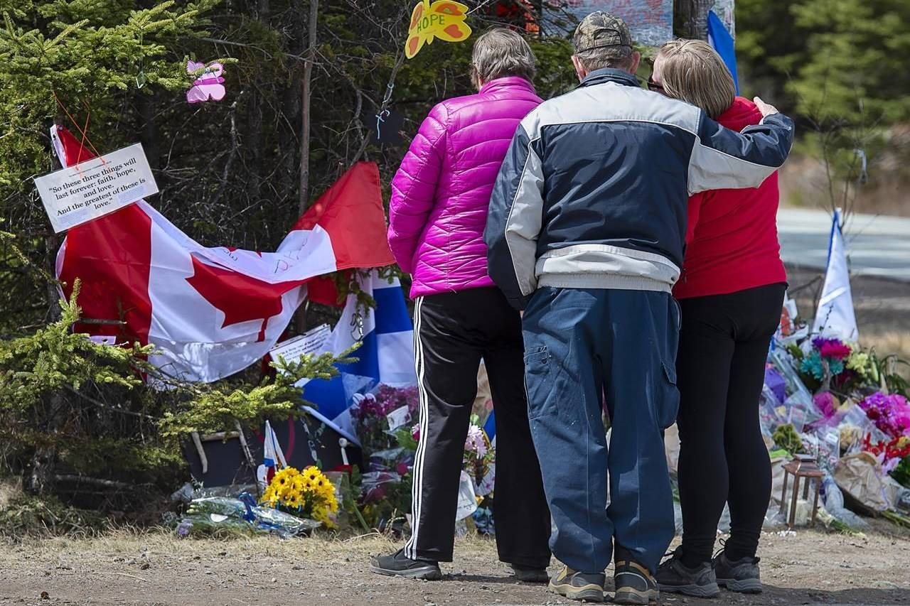 A family pays their respects to victims of the mass killings at a checkpoint on Portapique Road in Portapique, N.S. on Friday, April 24, 2020. As pressure mounts on the federal and Nova Scotia governments to call an inquiry into one of the worst mass killings in Canadian history, the country's leading scholar on inquiries says Ottawa and the province should do the right thing and work together on a joint inquest. THE CANADIAN PRESS/Andrew Vaughan