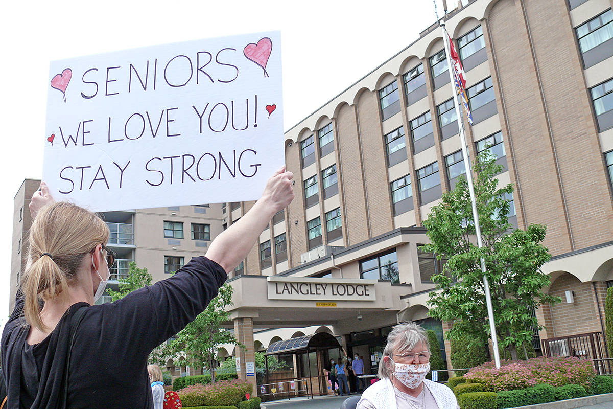 Health Care worker Angela Hay, a Murrayville resident, held up a sign of support with encouraging messages on both sides at a Wednesday demonstration of support at Langley Lodge (Dan Ferguson/Langley Advance Times)