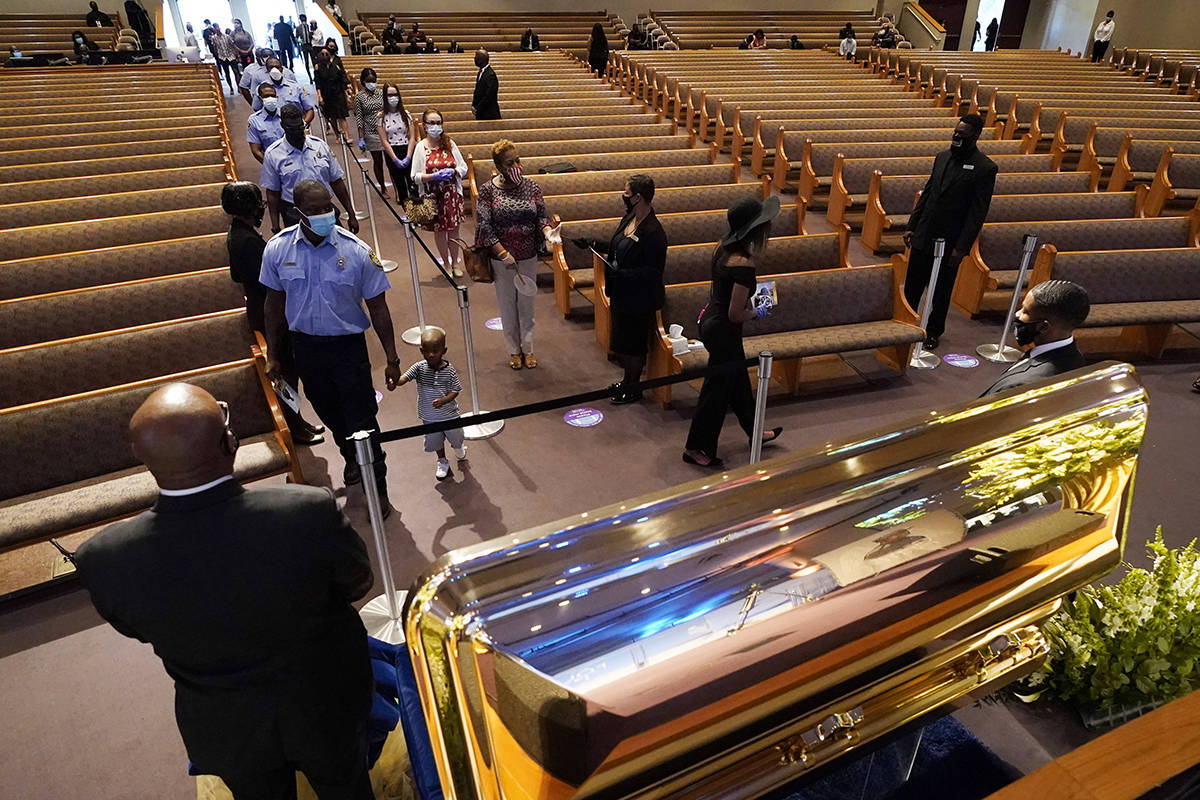 Mourners pass by the casket of George Floyd during a public visitation for Floyd at the Fountain of Praise church Monday, June 8, 2020, in Houston. (AP Photo/David J. Phillip, Pool)
