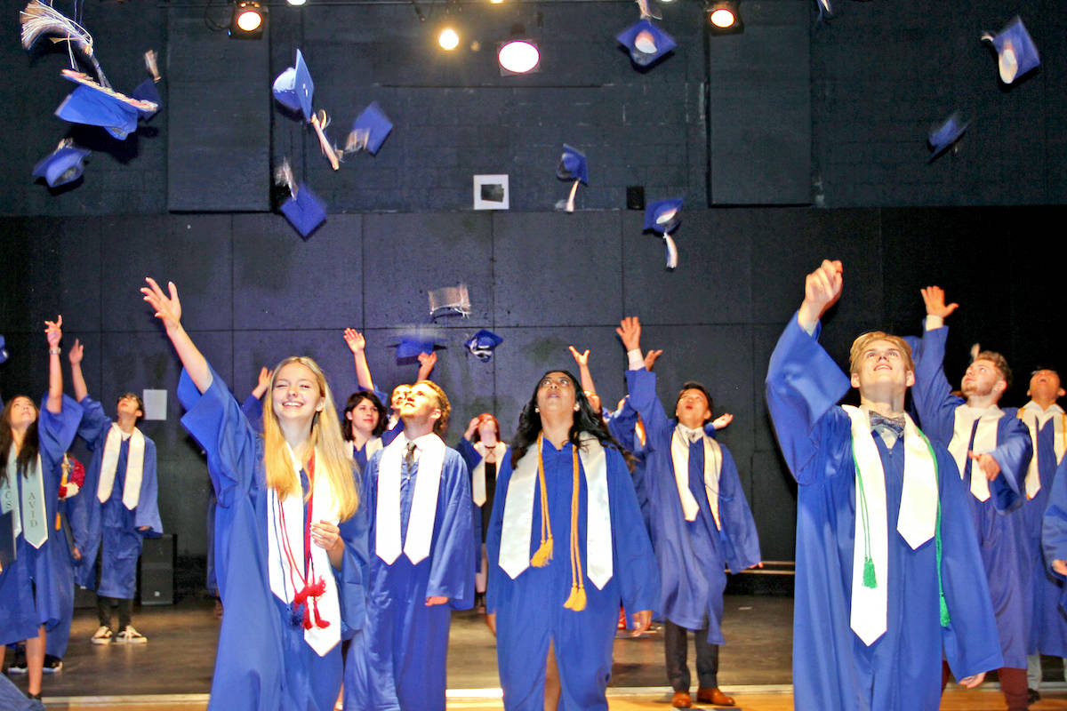 Aldergrove Community Secondary students including Devan-Marie Krys-Pratt (middle) carried on a long-held tradition amid the COVID- 19 pandemic – walking across the stage in cap and gown, and tossing their caps in celebration of their completion of high school. (ACSS/Special to the Star)