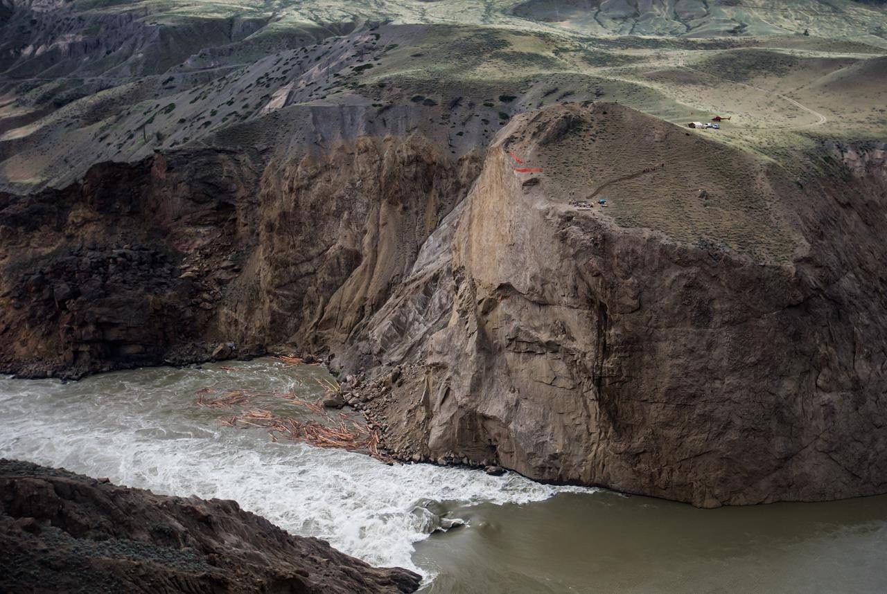 Workers are seen on the cliff at the site of a massive rock slide on the Fraser River near Big Bar, west of Clinton, B.C., on Wednesday July 24, 2019. Officials with the Department of Fisheries and Oceans say early arriving runs of Stuart and Chinook salmon were nearly wiped out after reaching the massive landslide along British Columbia's Fraser River last year. THE CANADIAN PRESS/Darryl Dyck