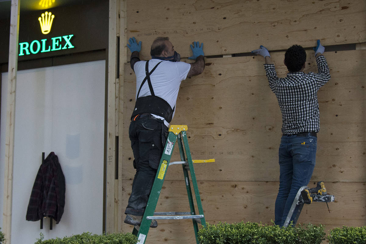Workers board up a luxury store in downtown Vancouver, B.C., Thursday, March 26, 2020. Businesses have been forced closed by the city and the province due to the COVID-19 outbreak. THE CANADIAN PRESS/Jonathan Hayward