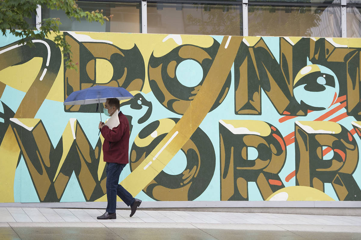 A pedestrian wears a protective face mask as they walk past mural in downtown Vancouver, Tuesday, June 2, 2020. Various businesses and restaurants are opening in the province as a part of the phase 2 reopening plan during the COVID-19 pandemic. THE CANADIAN PRESS/Jonathan Hayward