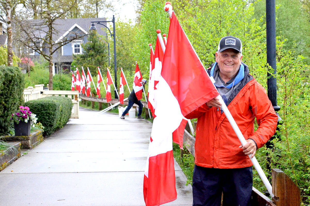 A Rotarian installs a Canadian flag in Fort Langley. (Ryan Uytdewilligen/Langley Advance Times)