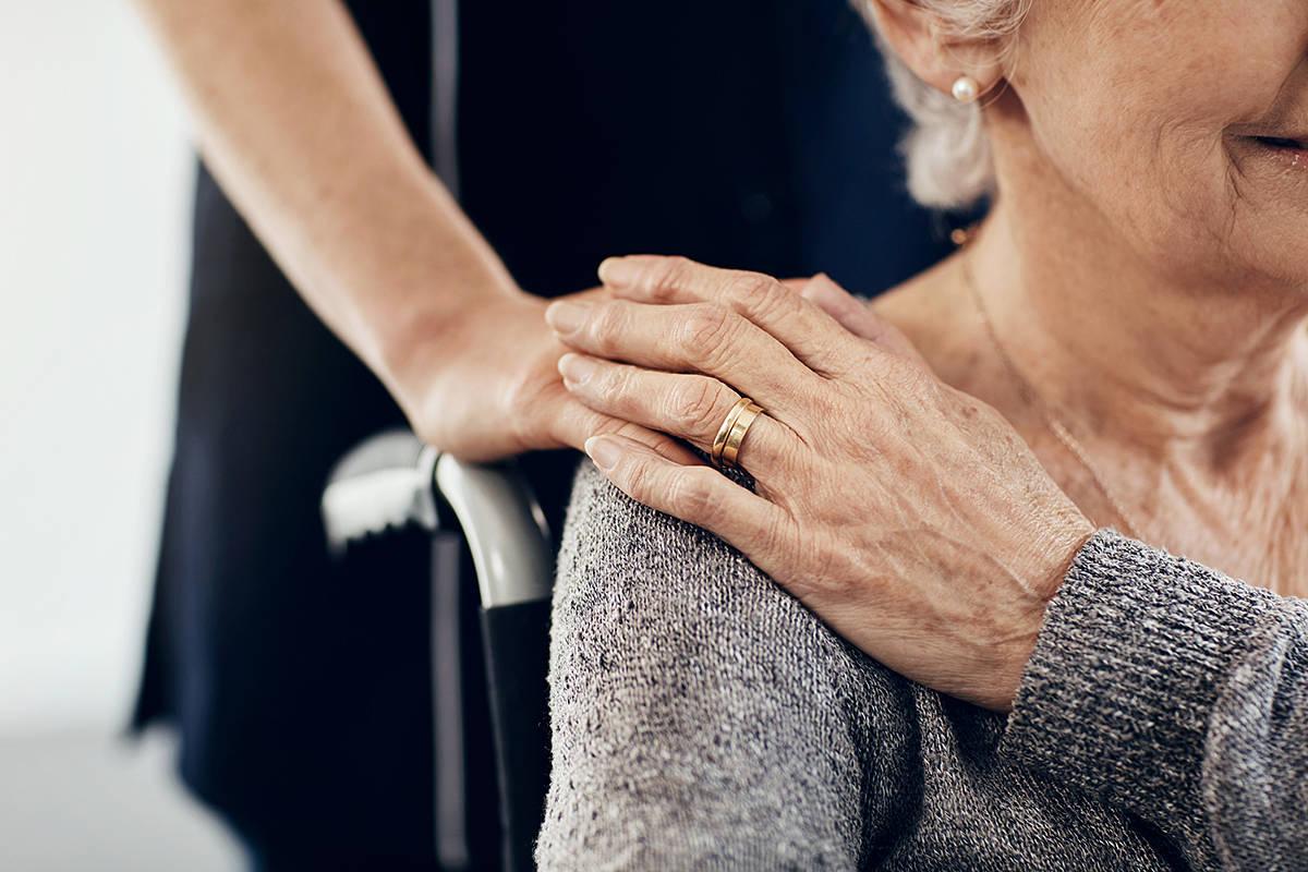 A female caregiver comforts a senior. (Yuri Arcurs Productions/Special to Black Press Media)