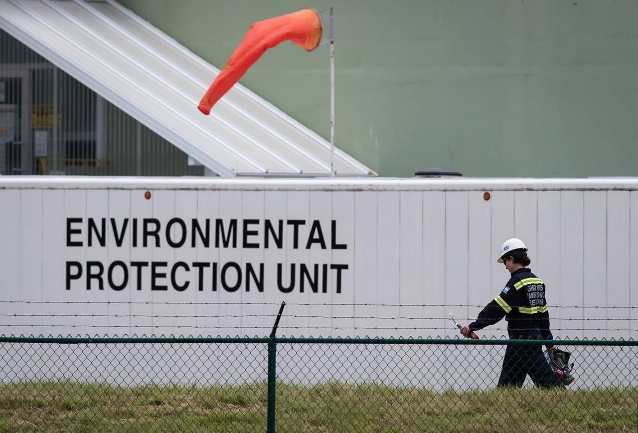 An emergency response worker carries an air monitoring device at the site of a crude oil spill at a Trans Mountain Pipeline pump station in Abbotsford, on Sunday, June 14, 2020. Trans Mountain estimates as much as 1,195 barrels of light crude spilled from the pipeline pumping station. While an investigation is ongoing, the Crown-owned company said in a statement the cause of the spill appears to be related to a fitting on a one-inch, or 2.5-centimetre, piece of pipe. THE CANADIAN PRESS/Darryl Dyck