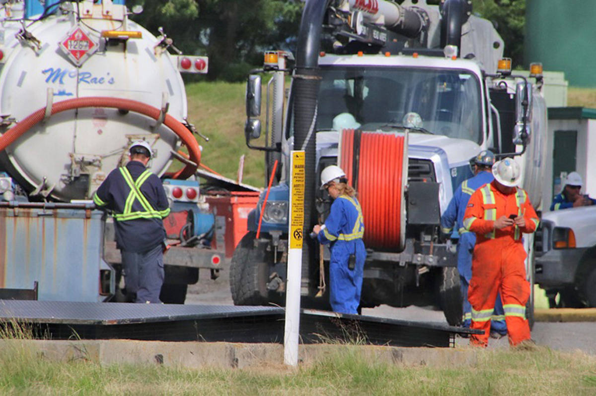 Workers clean up the oil spill in Abbotsford near Trans Mountain's Sumas Pump Station on Saturday, June 13, 2020. (Shane MacKichan file photo)