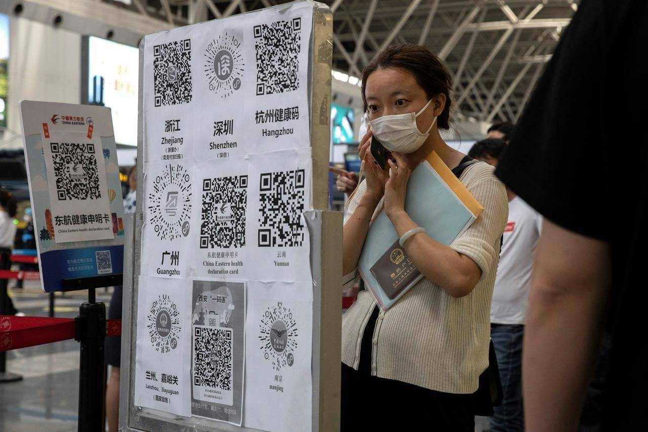 A passenger looks at a board with QR codes for health screening from different provinces at the Beijing Capital Airport terminal 2 in Beijing on Wednesday, June 17, 2020. The Chinese capital on Wednesday canceled more than 60% of commercial flights and raised the alert level amid a new coronavirus outbreak, state-run media reported. (AP Photo/Ng Han Guan)
