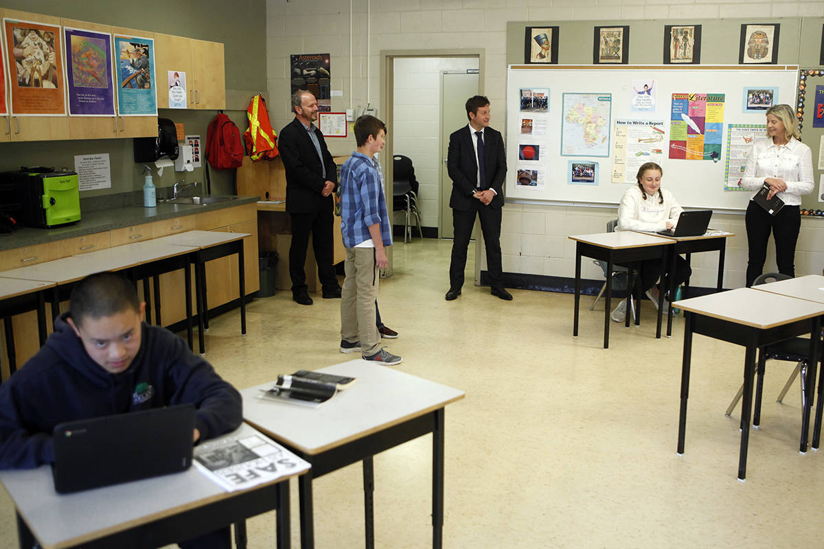B.C. Minister of Education Rob Fleming, centre, talks with Grade 7 teacher Lisa Galway as students return to part-time classes as he tours Monterey Middle School and in Victoria, B.C., on Tuesday, June 2, 2020. THE CANADIAN PRESS/Chad Hipolito