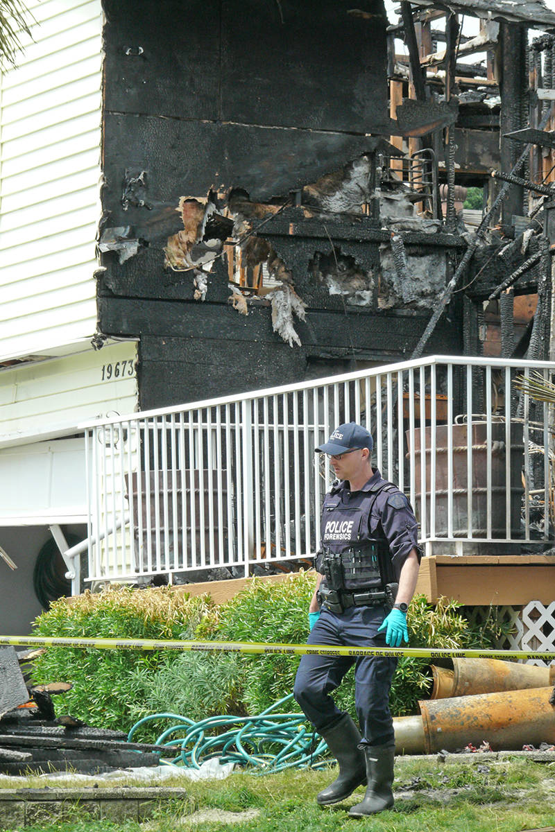 Officers remain at the scene of the charred remains of a Langley house in the 19600 block of Wakefield Drive where three bodies were found on June 13, 2020. (Dan Ferguson/Langley Advance Times)