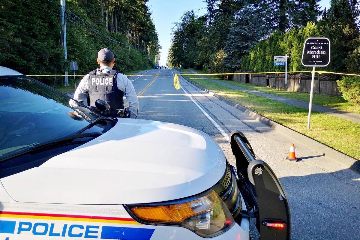 A Surrey RCMP officer blocks traffic along 168 Street at 28 Avenue Thursday morning, while police continue their investigation into a woman's death. The South Surrey thoroughfare remains closed to traffic, with northbound motorists diverted at 26 Avenue. (Tracy Holmes photo)