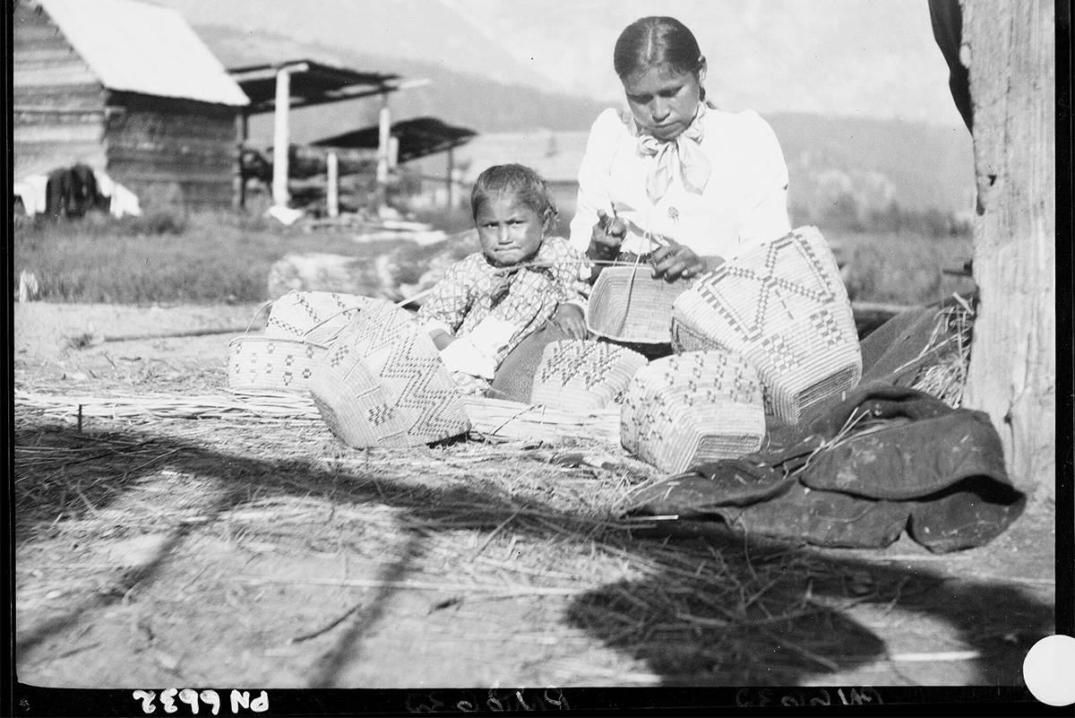 An image from the Royal BC Museum's digitized collection of historical photographs shows an Interior Salish woman and child weaving baskets. The image is one of thousands posted in an online database. (Courtesy of the Royal BC Museum)