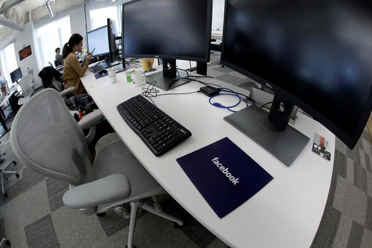 In this Jan. 9, 2019, file photo, Facebook employees sit at their stations during a tour of its new 130,000-square-foot offices in Cambridge, Mass. Facebook, Open Text and Shopify are transitioning to permanent work from home, but that will likely mean changes to compensation and salaries if you live or move somewhere not in the vicinity of your current office. THE CANADIAN PRESS/AP/Elise Amendola, File