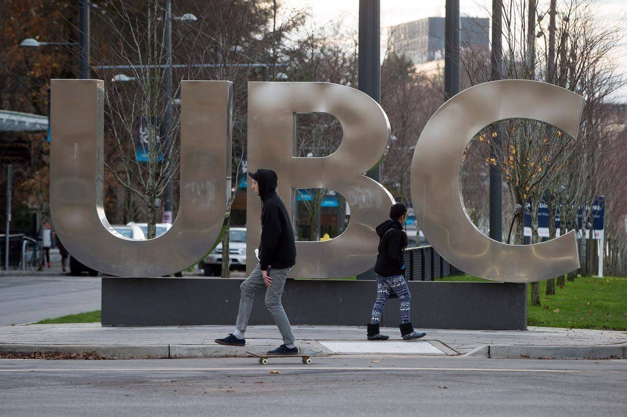A man on a skateboard and a young woman pass large letters spelling out UBC at the University of British Columbia in Vancouver, B.C., Sunday, Nov. 22, 2015. THE CANADIAN PRESS/Darryl Dyck