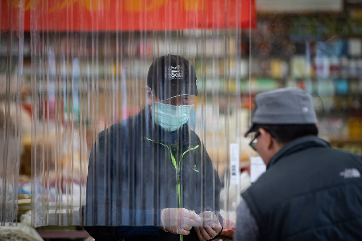 A man assists a customer from behind a plastic divider at a store in Chinatown, in Vancouver, B.C., Wednesday, June 10, 2020. THE CANADIAN PRESS/Darryl Dyck