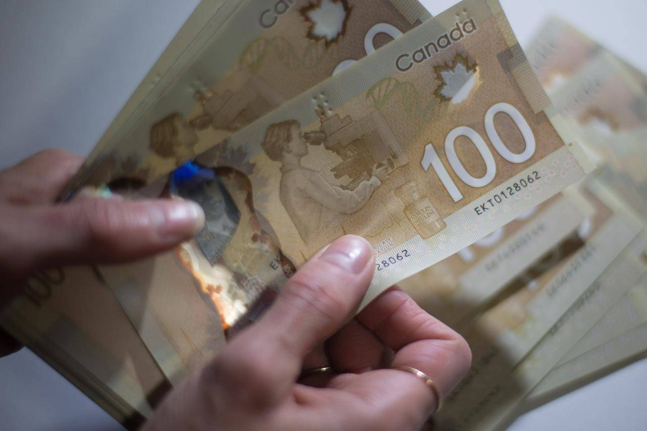 Canadian $100 bills are counted in Toronto, Feb. 2, 2016. The Conference Board of Canada says the economy may have already begun to recover from the deepest recession on record if the country can avoid another national COVID-related shutdown. THE CANADIAN PRESS/Graeme Roy