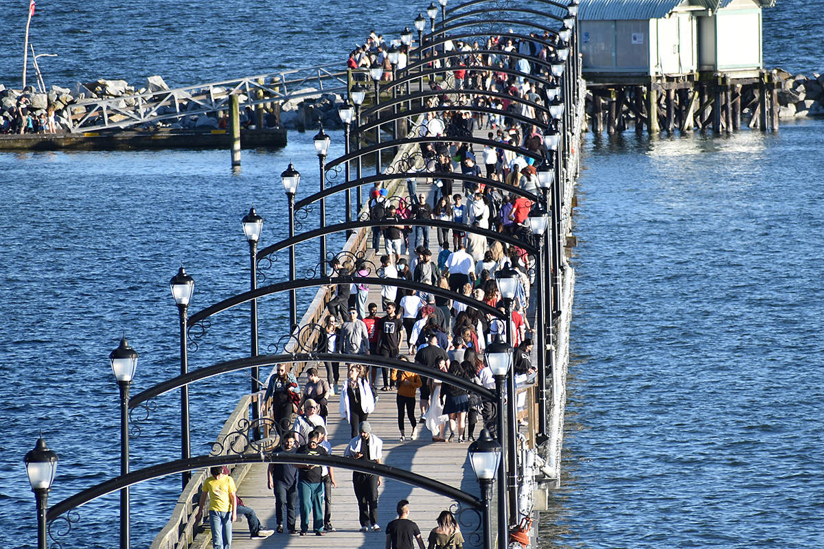 Crowds of people walked along the White Rock Pier Sunday evening. (Aaron Hinks photo)