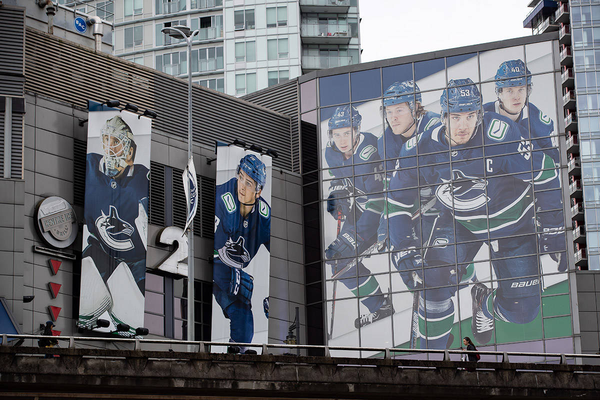 People walk on the Dunsmuir Viaduct as large photographs of Vancouver Canucks players Jacob Markstrom, Jake Virtanen, Quinn Hughes, Brock Boeser, Bo Horvat and Elias Pettersson are seen on the outside of Rogers Arena, home to the NHL hockey team, in Vancouver, on Monday, June 22, 2020. THE CANADIAN PRESS/Darryl Dyck