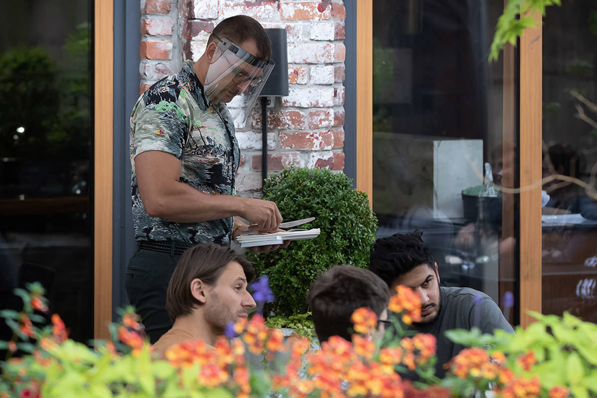 A server wears a face shield while working on the patio at Chambar restaurant in Vancouver, on Monday, June 22, 2020. THE CANADIAN PRESS/Darryl Dyck