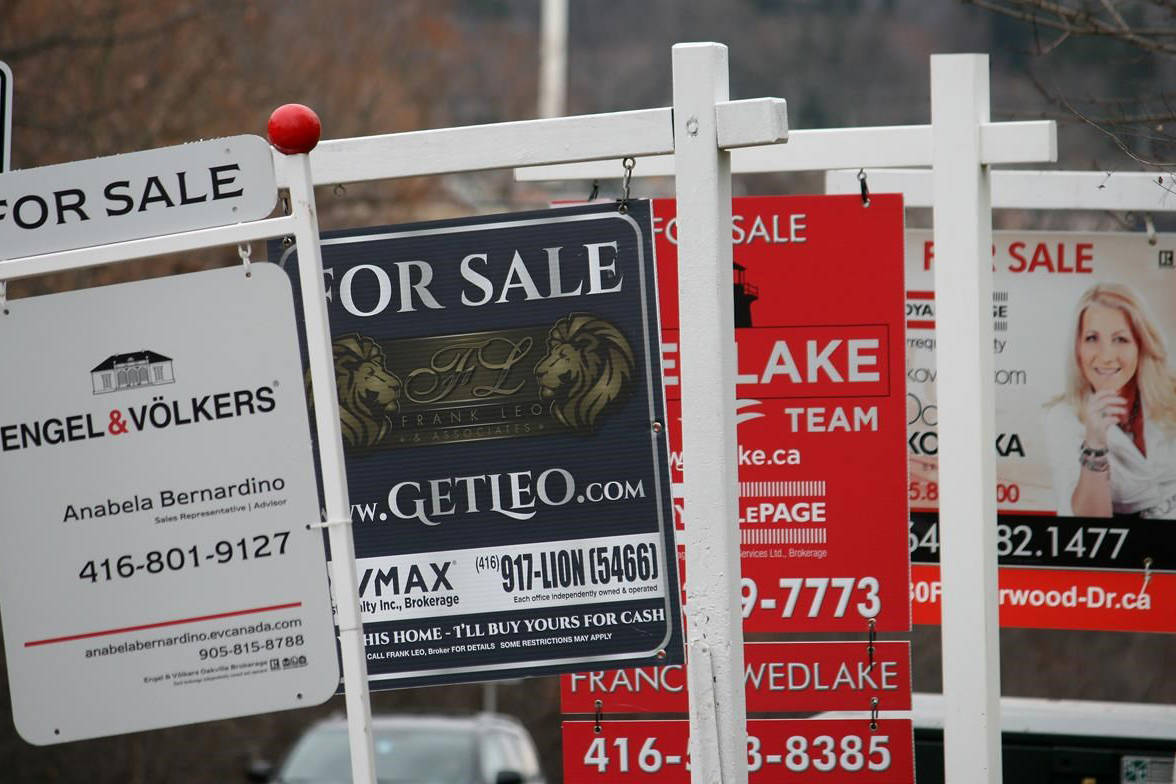 """Real estate for sale signs are shown in Oakville, Ont. on December 1, 2018. Canada Mortgage and Housing Corp. expects a drop in home prices in the country's biggest cities amid """"severe declines"""" in home sales and construction. The federal housing agency says a combination of factors related to the pandemic, such as higher unemployment and lower income, will slow housing starts and push sales and home prices below pre-COVID levels. CMHC says the market likely won't see a return to pre-pandemic levels before the end of 2022. THE CANADIAN PRESS/Richard Buchan"""