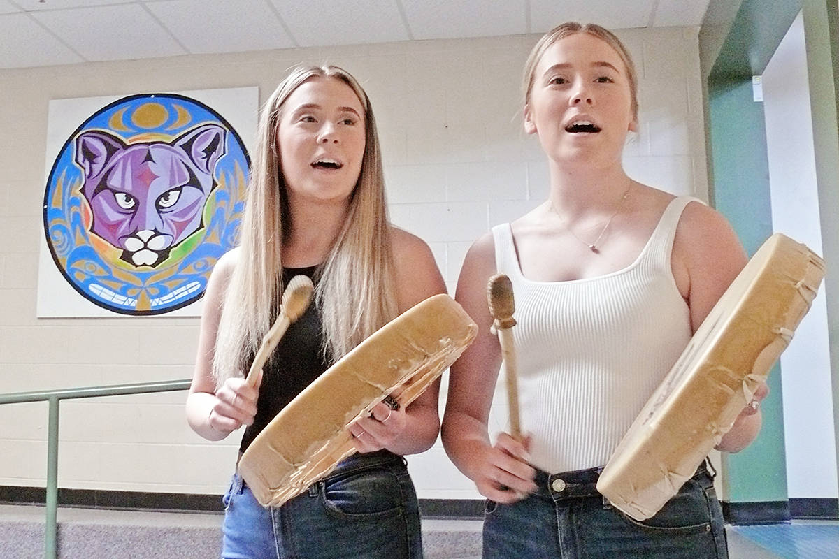 Twin sisters Kayla (left) and Krysta Serviss, members of the Shuswap First Nation, performed in front of the painting by artist Brandon Gabriel, which was this year's graduating class present to Parkside Centennial School in Aldergrove. Students and parents took part in a modified version of a grad walk through the school on June 24, 2020. (Dan Ferguson/Langley Advance Times)