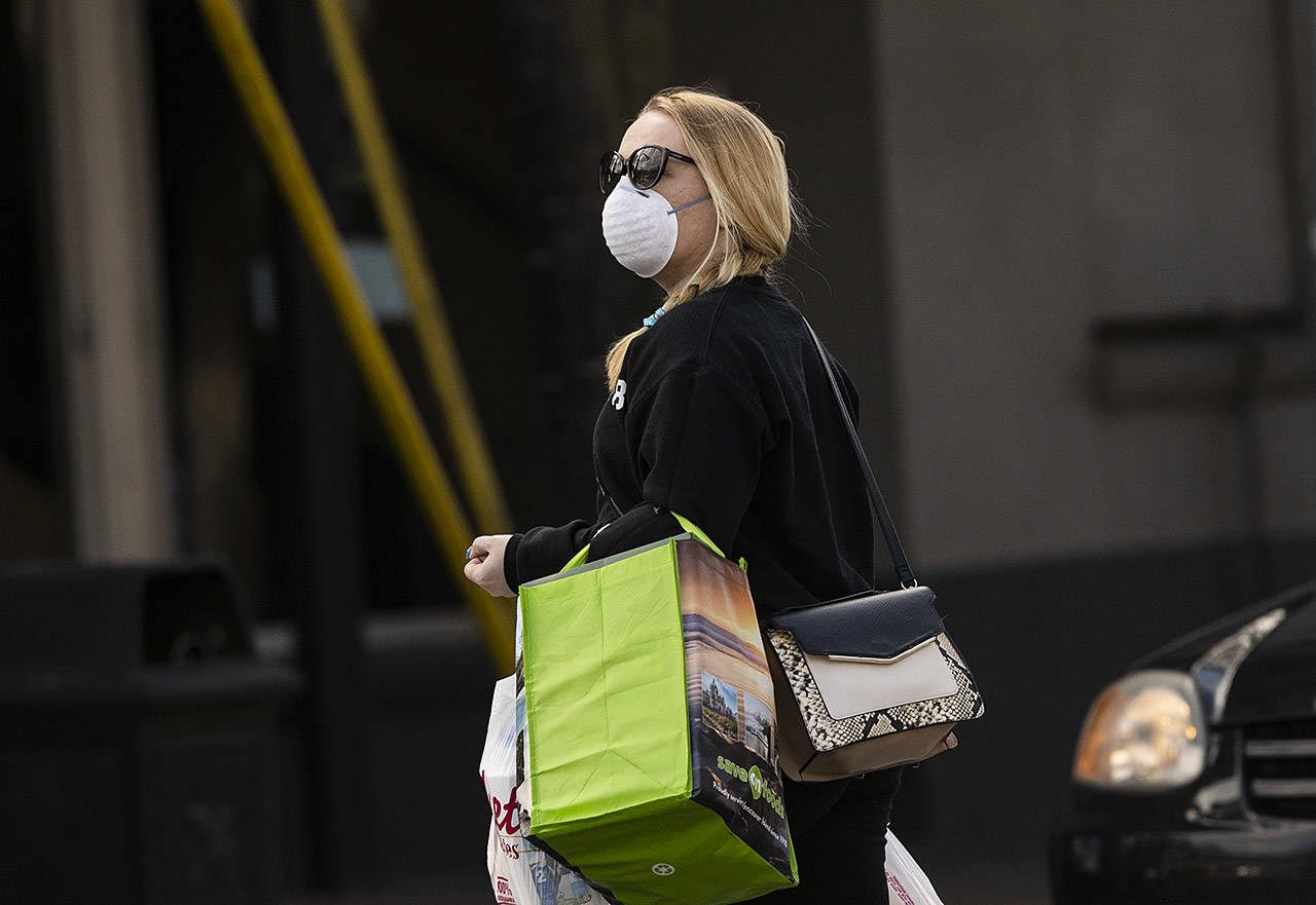 A woman with a mask on walks across View Street in Victoria. The streets of downtown Victoria are quieter than usual in the wake of physical isolation mandates from the provincial and federal governments in response to the COVID-19 pandemic. (Arnold Lim / Black Press)