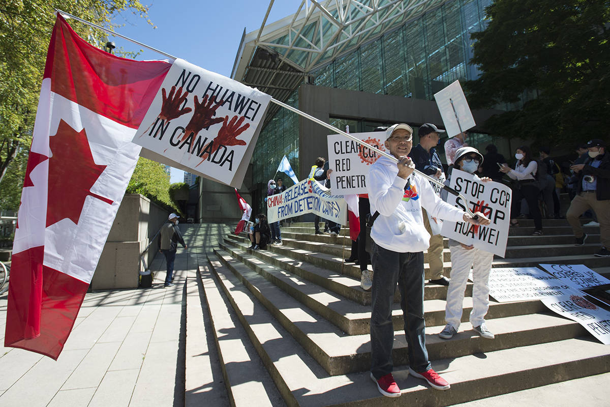 FILE – A crowd is pictured on the steps of B.C. Supreme Court as Meng Wanzhou, chief financial officer of Huawei, attends a session in Vancouver, Wednesday, May 27, 2020 as the judge reads the ruling of double criminality in the extradition of Wanzhou. THE CANADIAN PRESS/Jonathan Hayward