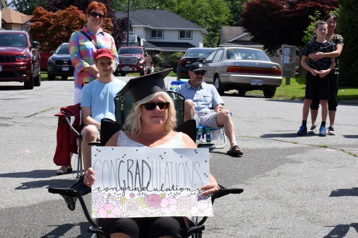 A combination of educational assistants, teachers, family and friends, socially distanced from one another, watch the graduation ceremony for Masato Wong. (Colleen Flanagan-THE NEWS)