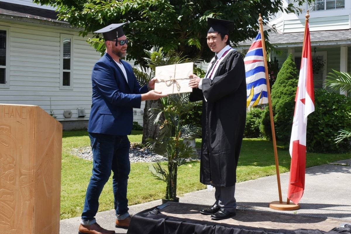 Ryan Neufeld hands Masato Wong his high school certificate during a ceremony outside Wong's home on Thursday. (Colleen Flanagan-THE NEWS)