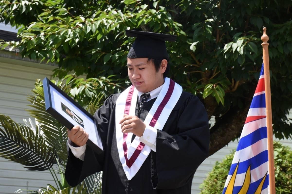 Masato Wong receives a framed graduation photo. (Colleen Flanagan-THE NEWS)