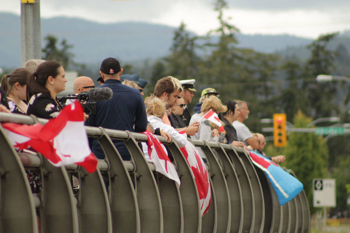 The crowd on Royal Oak Drive grew quickly as people waited patiently for the procession to come down Highway 17. (Devon Bidal/News Staff)
