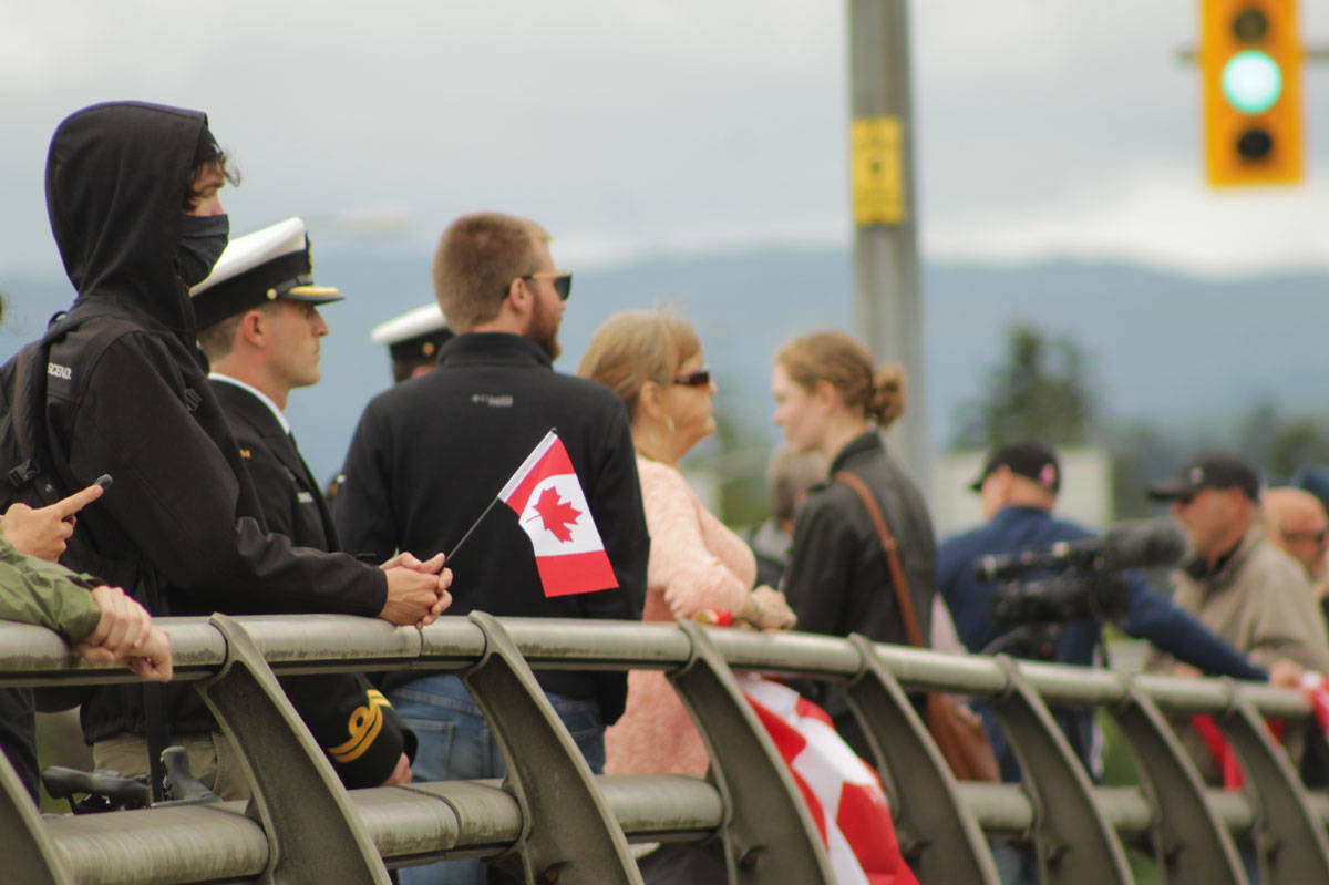People of all ages clutched Canadian flags and signs as they waited for the memorial procession to come down Highway 17. (Devon Bidal/News Staff)