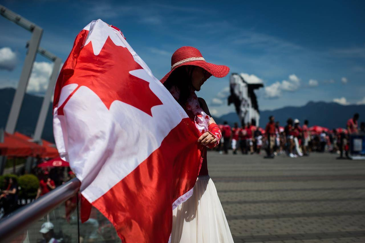Summer Shen waves a Canadian flag while sporting a patriotic outfit during Canada Day celebrations in Vancouver, on July 1, 2019. The true north remains just as strong but might not feel quite as free with Canada Day celebrations being a little quieter and physically distant as people keep their guard up against COVID-19. From coast to coast to coast the usual festivities, parades and fireworks that accompany Canada Day have been cancelled in many communities this year because of COVID-19, but Canadians are still finding ways to mark the country's birthday. THE CANADIAN PRESS/Darryl Dyck