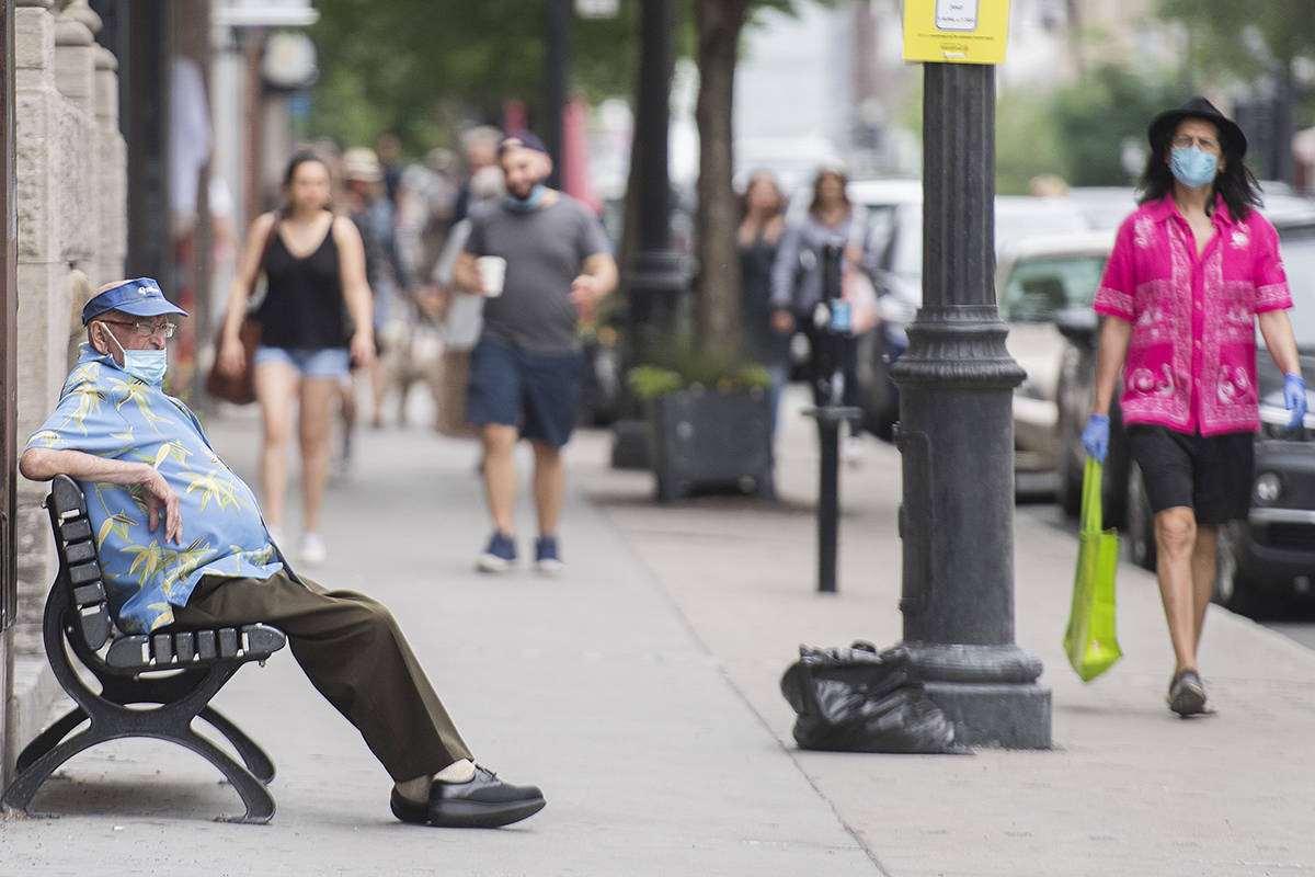 A man wears a face mask as he sits on a bench in Montreal, Saturday, June 27, 2020, as the COVID-19 pandemic continues in Canada and around the world. THE CANADIAN PRESS/Graham Hughes